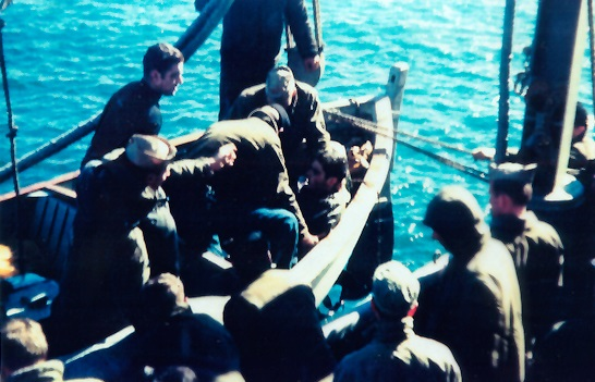 Lou Ives being helped out of whaleboat by USS Hailey crew.