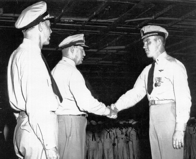 VADM H, J. Clark, Commander Seventh Fleet, congratulates LTjg G. E. R. Kinnear of VA-45 upon being awarded the Air Medal and Commendation Ribbon for outstanding performance of duty while operating against enemy forces in Korea. LTjg Kinnear is embarked aboard the USS Lake Champlain (CVA-39). 1953